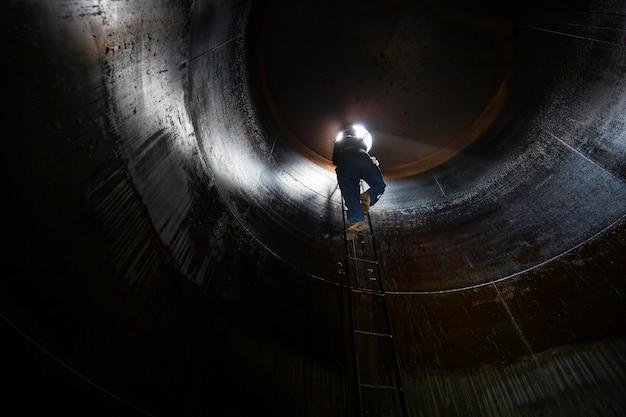 Macho dentro suba a escada de armazenamento de inspeção visual do tanque de óleo combustível pesado no espaço confinado