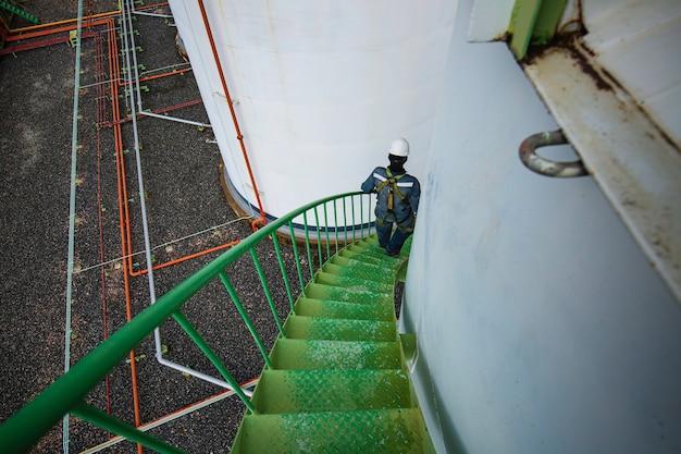 Macho descendo as escadas do tanque de armazenamento de registro visual de inspeção da escada na lateral.