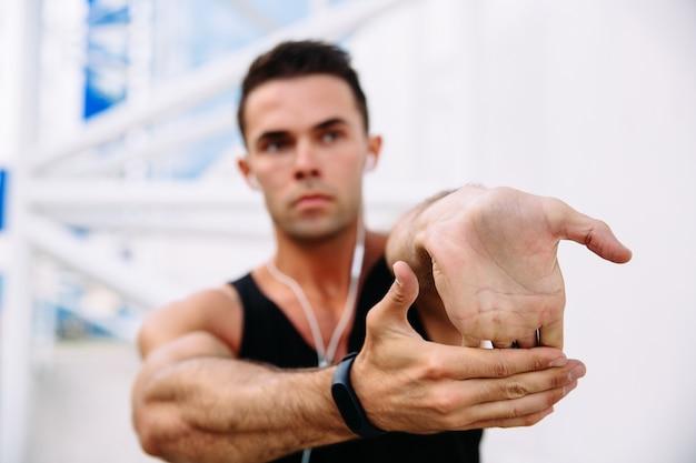 Macho do atleta nos fones de ouvido ao esticar seus braços, preparando-se para exercitar ao ar livre.