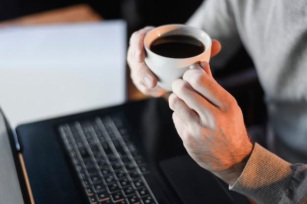 Macho do close-up que guarda a xícara de café