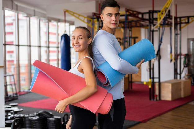 Macho e fêmea na aula de fitness com esteira