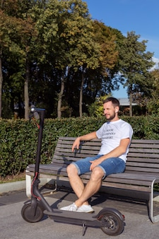 Macho em camiseta branca, sentado num banco com seu escooter em um parque ao ar livre em tempo ensolarado