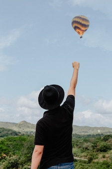 Macho em pé com o braço e o punho levantado no ar e um balão de ar quente voando no fundo