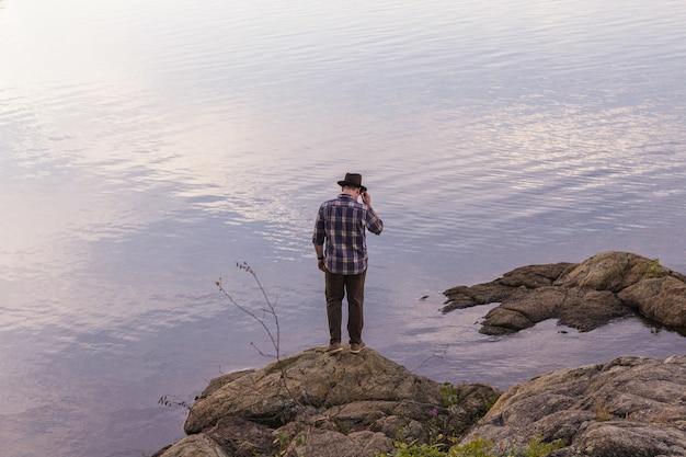 Macho em pé sobre uma rocha perto de um mar, olhando para baixo
