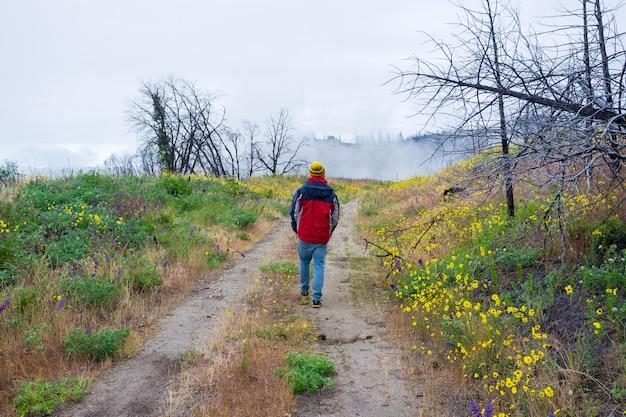 Macho em um casaco quente andando em uma estrada estreita em um belo campo