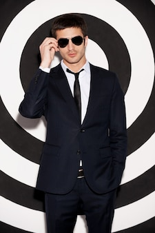 Macho encantador. jovem bonito com um terno completo ajustando os óculos de sol em pé contra um fundo preto e branco