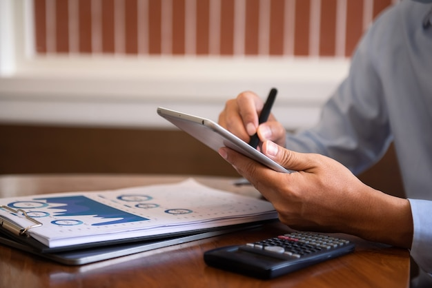 Macho escreve o empresário de informações trabalhando no tablet, escrevendo o plano de negócios enquanto está sentado no café pela manhã.