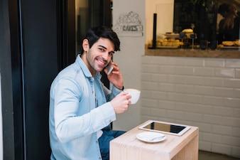 Macho falando no smartphone sentado no café