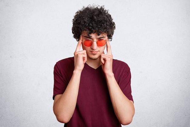 Macho focado pensativo, com cabelos nítidos, tem expressão concentrada séria, usa óculos de sol vermelhos, isolados sobre o branco