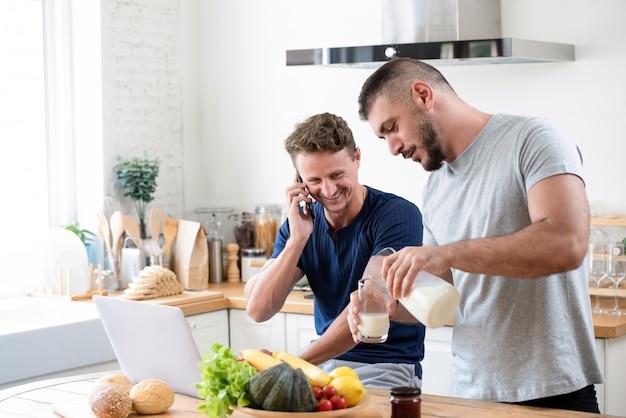 Macho gay feliz preparando o café da manhã para seu parceiro em casa