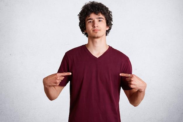 Macho jovem bonito indica no espaço em branco da camiseta casual para o seu anúncio ou design de conteúdo, tem cabelo nítido, posa na parede de concreto branco. olhe para minhas roupas novas.