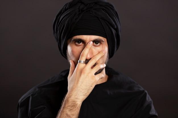 Macho jovem bonito no turbante muçulmano. fundo preto