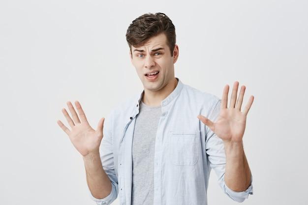 Macho jovem ofendido caucasiano tem reação precipitada sobre o que ouviu, levanta as mãos, como dizer para parar com isso, tem expressão de desagrado e raiva, isolado.