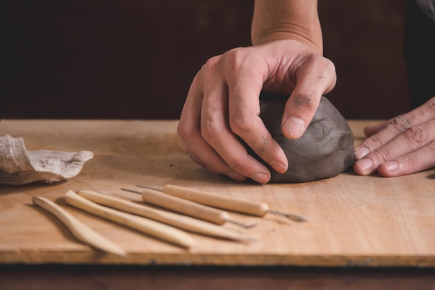Macho mãos modelando um bloco de barro na mesa de madeira