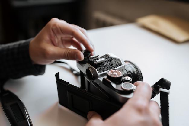 Macho mãos recarregando câmera retro filme sobre uma mesa branca