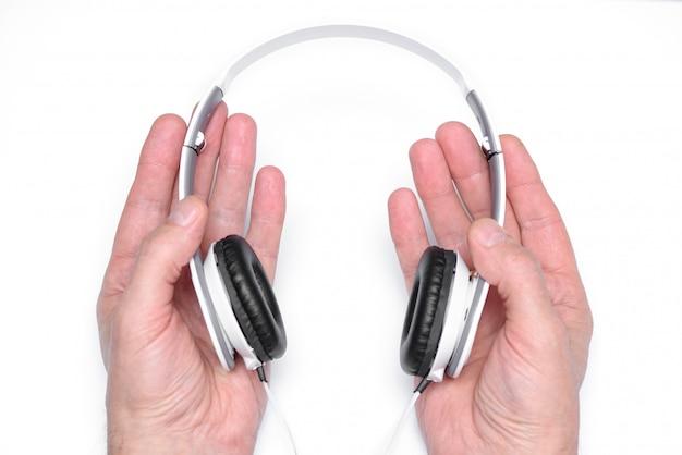Macho mãos segurando fones de ouvido brancos
