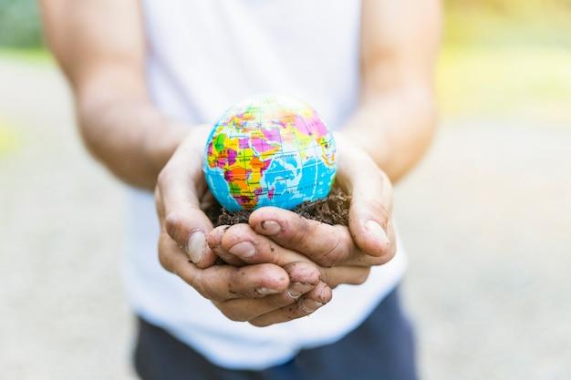 Macho mãos segurando um pequeno globo