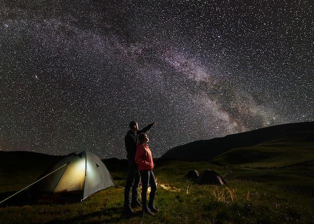Macho mostra fêmea no céu estrelado da noite na via láctea contra o pano de fundo das montanhas