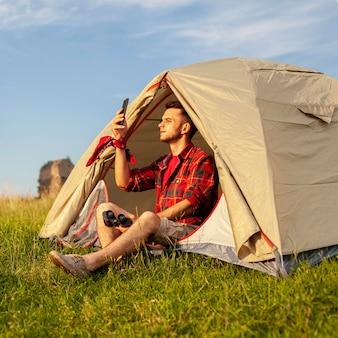 Macho na barraca de acampamento ao pôr do sol, a tirar uma selfie