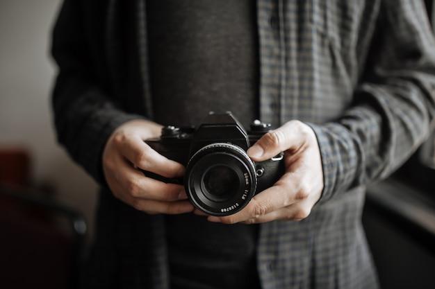 Macho nas mãos de homem de camisa escura possui câmera retro