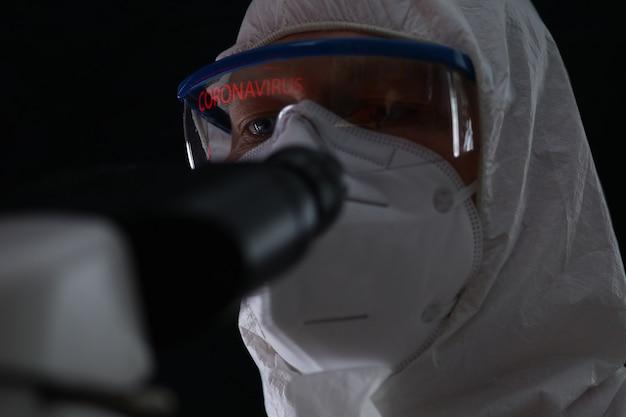 Macho no bioquímico de traje de proteção monitorando o coronavírus chinês