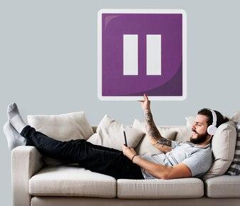 Macho no sofá segurando um ícone de botão de pausa