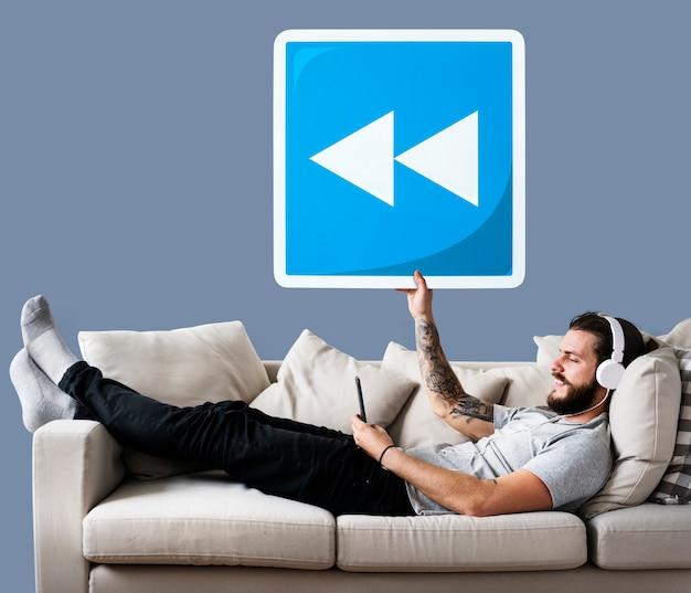 Macho no sofá segurando um ícone de botão de rebobinar