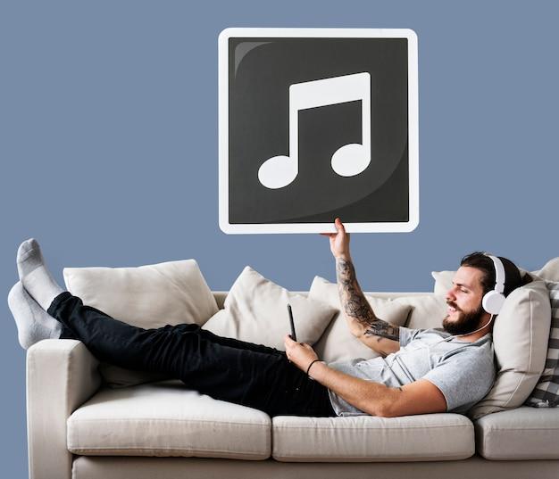 Macho no sofá segurando um ícone de nota musical