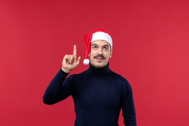 Macho normal de vista frontal com tampa vermelha de férias em fundo vermelho