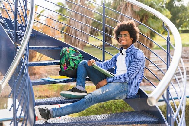 Macho novo com livro e sacos que relaxam na escadaria azul no parque