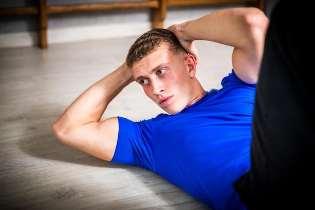 Macho novo do close-up no exercício da ginástica
