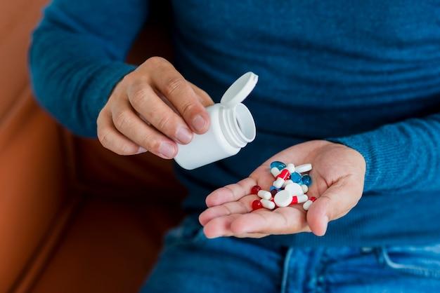 Macho novo do close-up que toma comprimidos