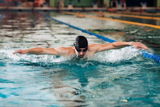 Macho novo no treinamento da piscina