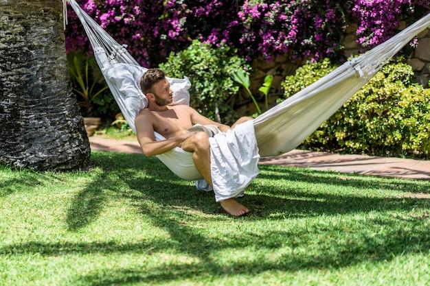 Macho nu que relaxa em uma rede no jardim.