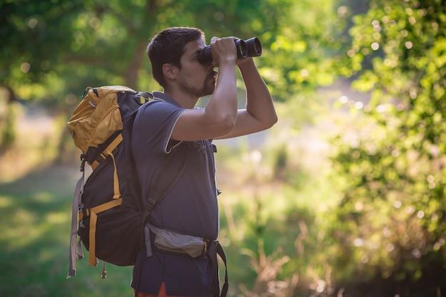 Macho olhando através de binóculos na floresta