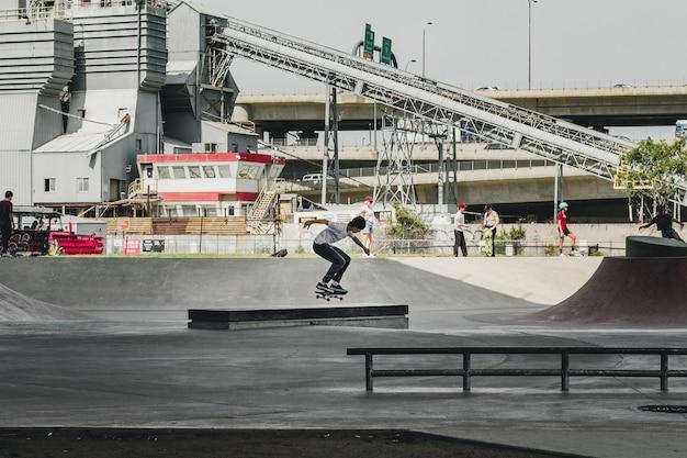 Macho patinando no parque de skate com construção e pessoas
