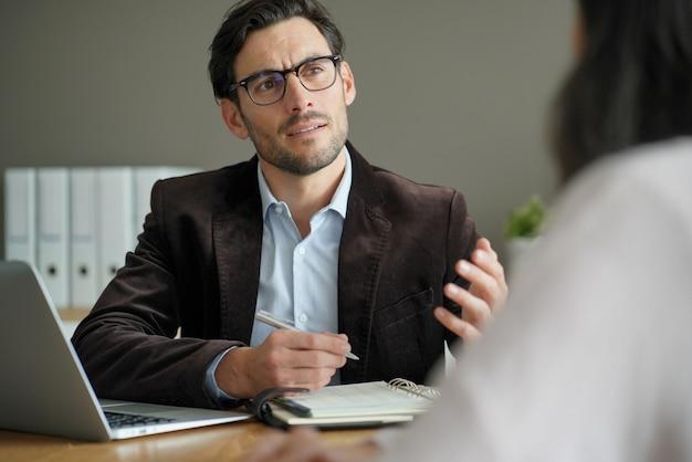 Macho profissional inteligente com o cliente no escritório
