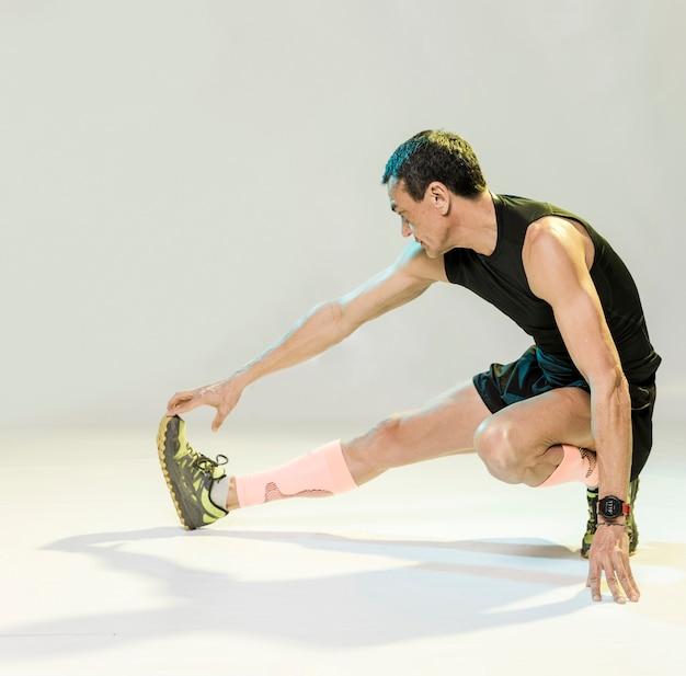 Macho que estica antes de exercitar