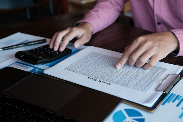 Macho que usa a calculadora e o portátil do computador para analisar o mercado de valores de acção