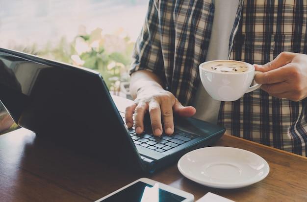 Macho que usa um computador com o copo de café na tabela de madeira.