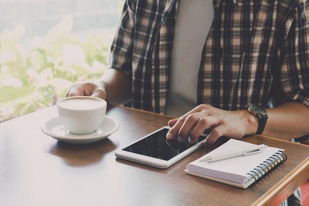 Macho que usa um telefone esperto com o copo de café na tabela de madeira.
