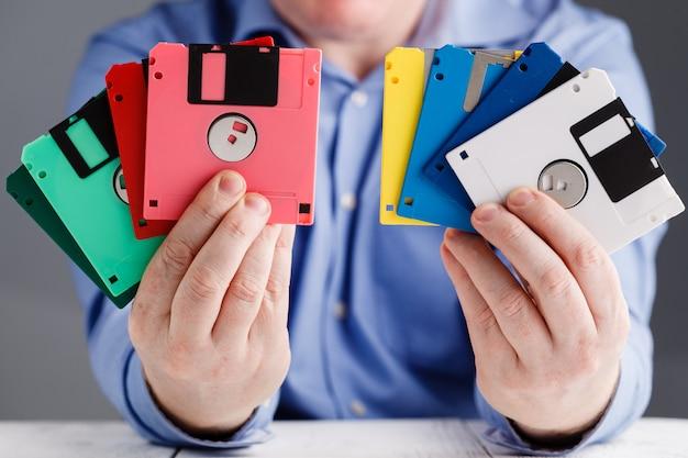 Macho segura disquete nas mãos, retro armazenamento