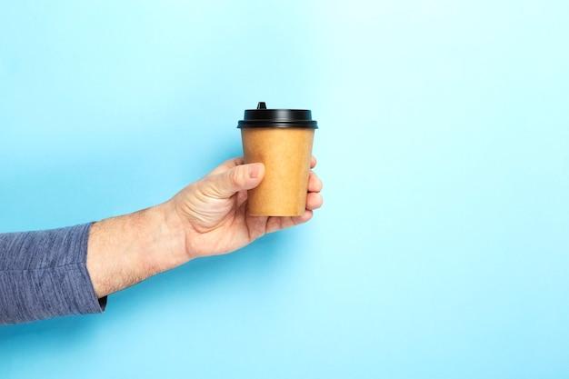 Macho segura o copo de papel de mão com café sobre fundo azul