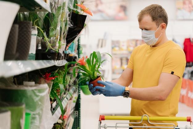 Macho segura um vaso de plantas, faz compras em uma grande loja de departamentos, usa máscara facial descartável e luvas de borracha