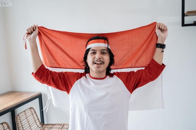 Macho segurando a bandeira indonésia. conceito de nacionalismo patriótico