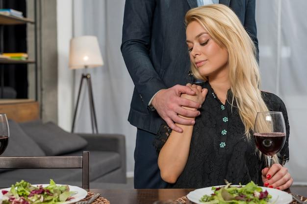 Macho segurando a mão da encantadora mulher loira na mesa