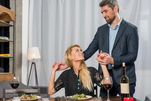 Macho segurando as mãos de mulher loira alegre na mesa