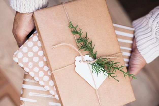 Macho segurando caixas de presentes em envoltórios