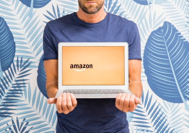 Macho segurando laptop com o site da amazon