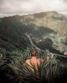 Macho sem camisa, sentado na grama alta em uma colina alta com falésias ao fundo